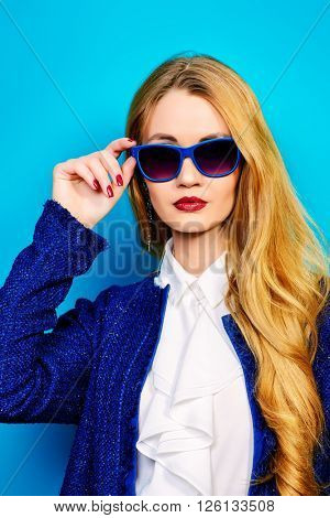 Vogue shot of the elegant young woman in sunglasses over bright aquamarine background.