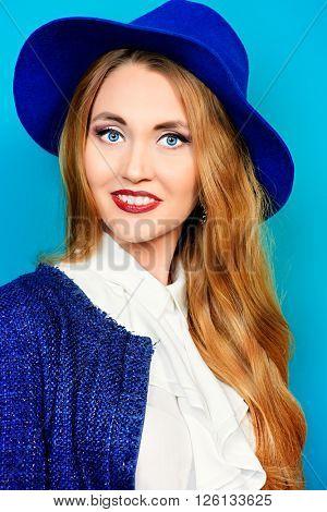 Fashion shot of the elegant young woman over bright aquamarine background.