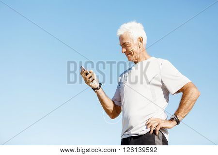 Male runner with his mobile smart phone standing outdoors