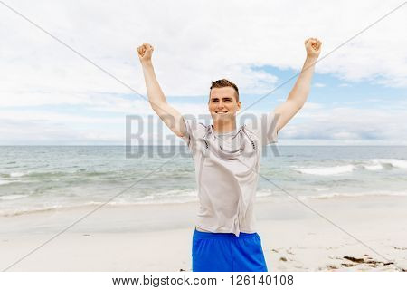 Young man in sport wear with outstretched arms
