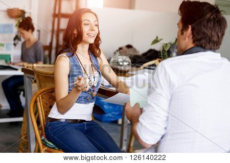 Young woman in office talking to her colleague