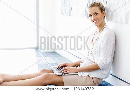 Attractive office worker sitting on floor