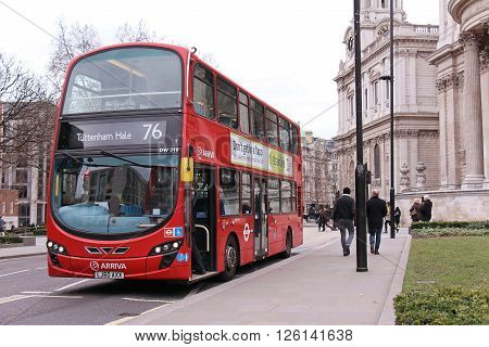LONDON UNITED KINGDOM - FEBRUARY 10: Famous red TFL public transport bus on a stop near Millennium bridge with people walking by in London UK - February 10 2015; Traditional red London bus with open front door for passengers to walk in