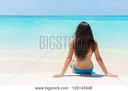Beach relaxation bikini suntan woman lying down relaxing sunbathing sun tanning on perfect white sand and pristine turquoise water. Idyllic tropical getaway luxury island life.