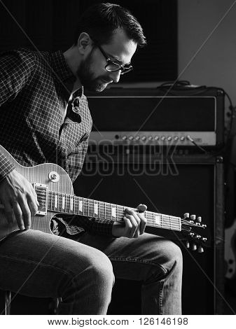 Photo of a man sitting playing his electric guitar in front of a large amplifier.