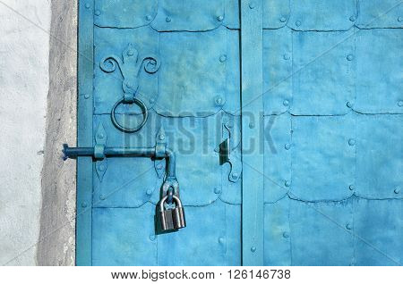 Architectural vintage background - old pale blue metal door with plates and aged metal door handle in the form of stylized lily.