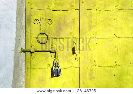 Aged bright yellow steel door with rivets and aged metal door handle in the form of stylized lily. Grunge architectural background.