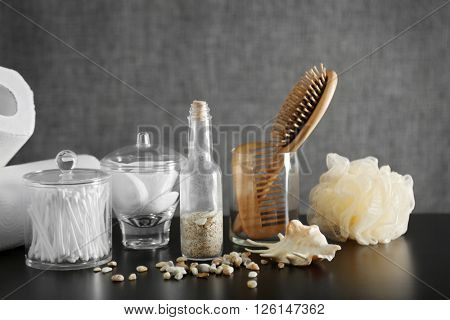Bathroom set with wooden comb, paper towels and sponges on grey background