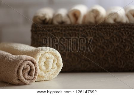 Wicker basket with towels inside on wooden table background