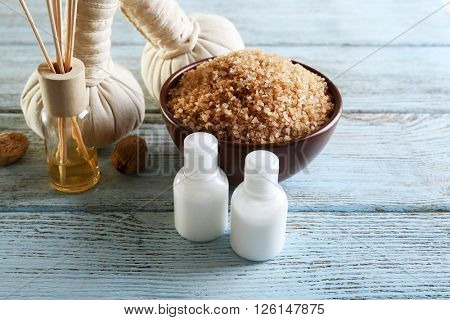Spa treatment with sea salt and oils on wooden background