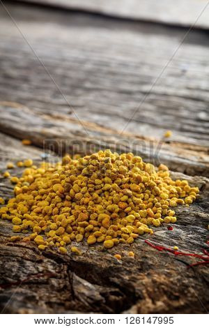 Bee pollen pile set on old wooden surface