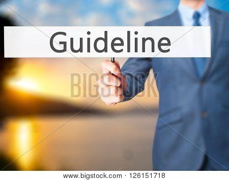 Guideline  - Businessman Hand Holding Sign