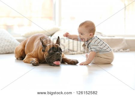 Little baby boy with boxer dog on the floor at home