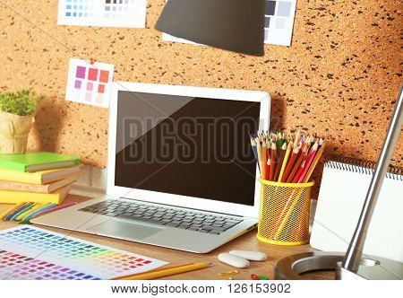 Workplace with laptop on light wooden table.