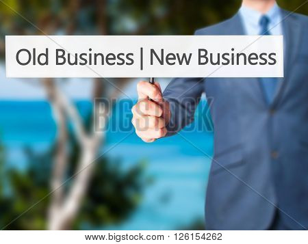 Old Business  New Business - Businessman Hand Holding Sign