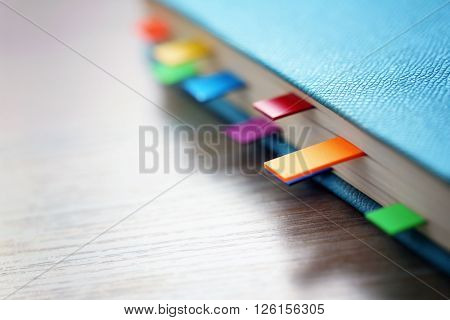 Blue dairy with multicoloured stickers on wooden background, closeup