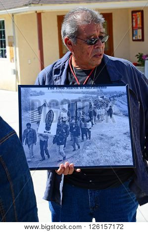 DELANO, CA - APRIL 17, 2016: A man who participated in Cesar Chavez's historic 1966 march to Sacramento shares a photograph with today's members of the march for agricultural workers' rights.