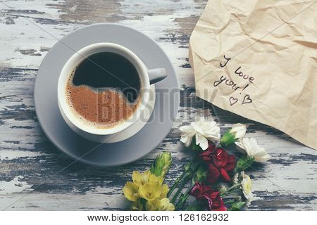 Cup of coffee, flowers and piece of crumpled paper with note I LOVE YOU on wooden table, top view