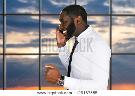 Happy afro man with cellphone. Businessman with phone at sunset. He deserved a promotion. It was a right decision.