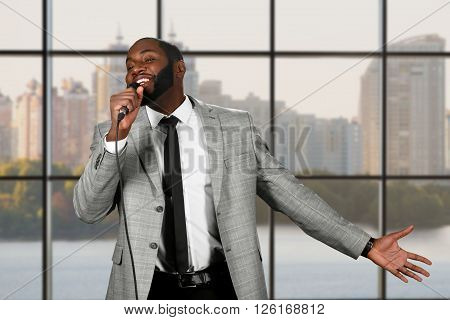 Black guy sings into microphone. Young singer on city background. So much passion. Audience will be charmed.