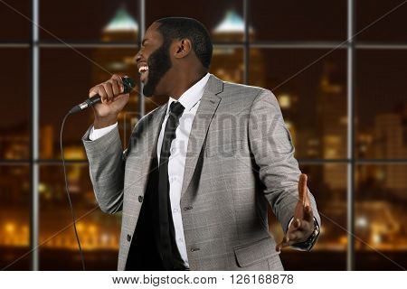 Expressive black singer with microphone. Vocalist on night city background. Blues performance in capital city. His voice is unbelievable.