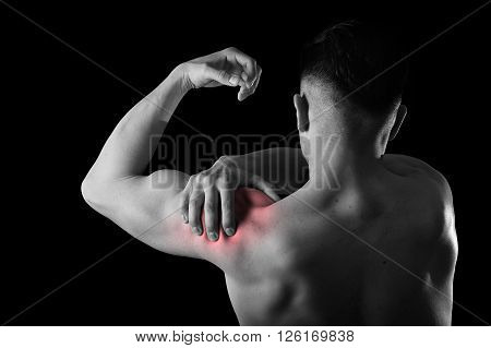 young muscular sport man holding sore shoulder with hand touching or massaging in workout stress body pain and health problem isolated black and white red spot injury