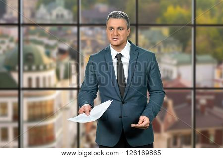 Adult businessman holding papers. Mature executive on urban background. Making a suggestion. Give me a signature.