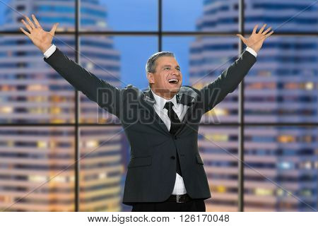 Joyful man with arms raised. Victorious official on skyscraper background. Another day another victory. News on the jackpot. ** Note: Visible grain at 100%, best at smaller sizes