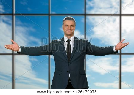Adult businessman's welcoming gesture. Polite executive on sky background. Best chief ever. It's all for you.
