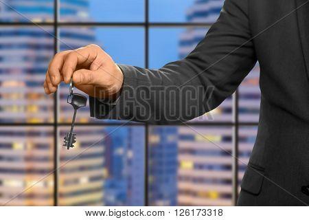 Hand of businessman holding key. Estate agent on evening background. The new apartment is yours. Special gift for company employee.