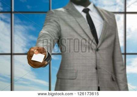 Afro businessman giving visit card. Presentable man on sky background. Sudden appearance of security inspector. Visitor in company headquarters.