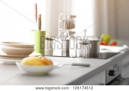 Modern table and electric stove with utensils in the kitchen beside window