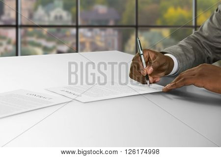 Black businessman's hand signs contract. Man signing contract at daytime. Opportunity to get great job. Safety is guaranteed.