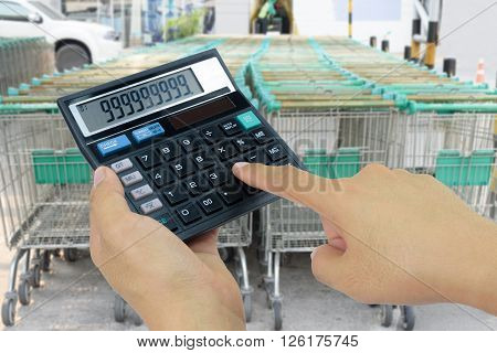 Hand holding a calculator on blurred image row Shopping Cart background