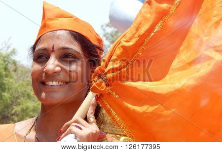HYDERABAD,INDIA-APRIL 15:Portrait of an Indian Hindu woman waving saffron flag a tradition during sri ram navami festival celebrations on April 15,2016