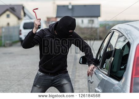 Car Thief Breaking A Glass In Car With Crowbar