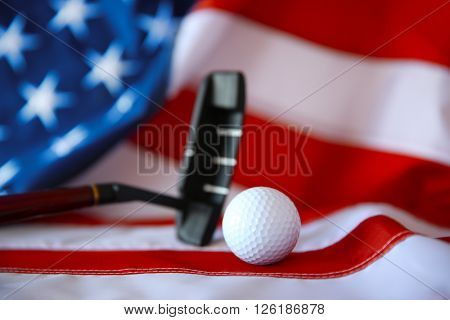 Golf ball and club on background of American flag. Popular sport concept