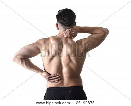 back view of young man with muscular body holding his neck and low back suffering pain in sport spinal injury and fitness stress isolated on white background