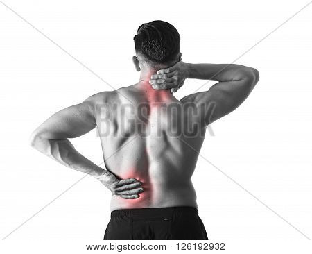 back view of young man with muscular body holding his neck and low back suffering pain in sport spinal injury and fitness stress isolated on black and white with red spot sore area