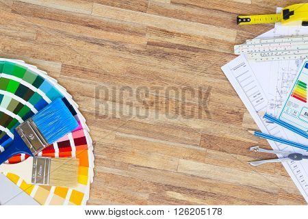 Interior designer's working desktop with  architectural plan of the house, color palette and  brushes, copy space on wooden table