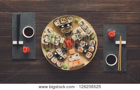 Japanese food restaurant, sushi maki gunkan roll plate or platter set. Set for two with chopsticks, ginger, soy, wasabi. Sushi at rustic wood background and black stone. Top view at wood