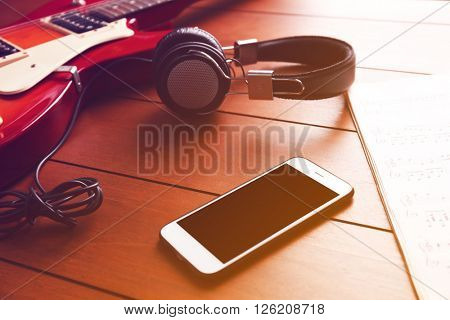 Electric guitar with headphones and mobile phone on wooden background