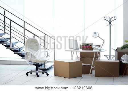 Moving cardboard boxes and personal belongings near stairs in office