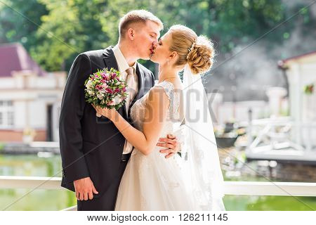 Wedding, Beautiful Romantic Bride and Groom Kissing and Embracing at Sunset