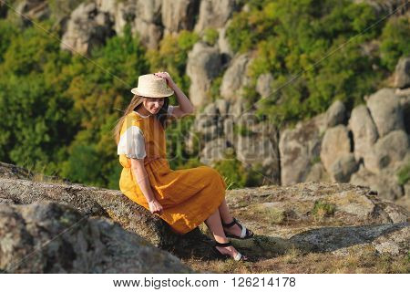 Happy Girl Sits On A Background Of The Canyon