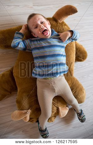 Little boy indulges in lying on a soft toy dog