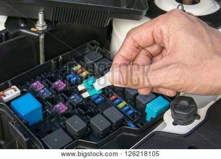 Auto mechanic checking a car fuse. mechanic, auto, fuse, closeup, automotive