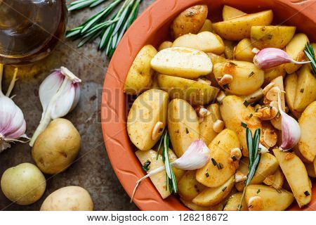 Sliced raw potatoes in a clay baking dish before baking in the oven with spices garlic rosemary olive oil. Dinner in a rustic style. Selective focus