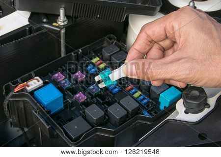 Auto mechanic checking a car fuse. mechanic, auto, fuse,