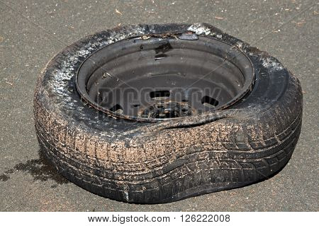 Dirty deflated damaged tire on rim due to blowout